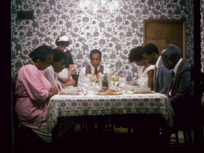 The Mundys and the Richardsons sit at the table and say grace before dinner