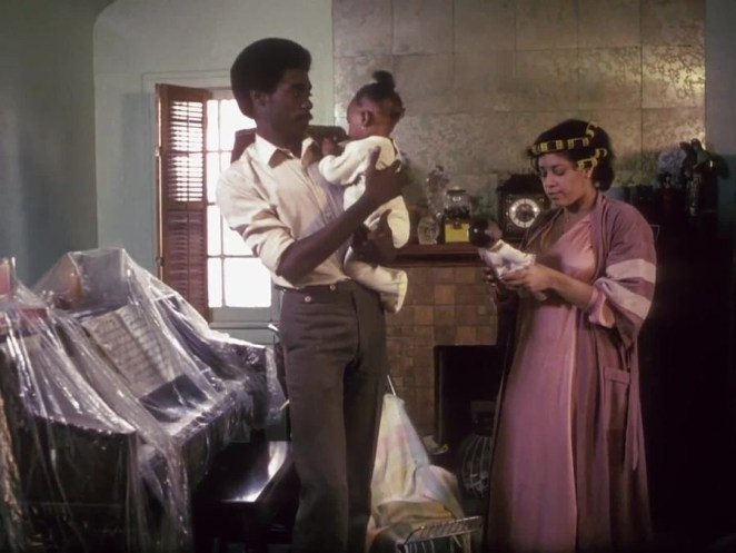 Pierce (Everett Silas) holds a baby and talks to a woman in curlers.