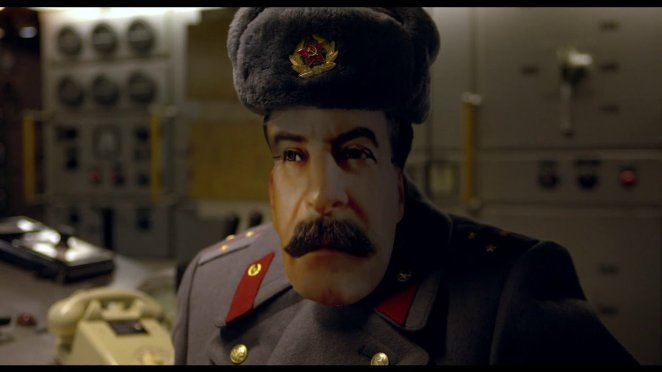 a Soviet army officer wears a mask of saddam hussein's face