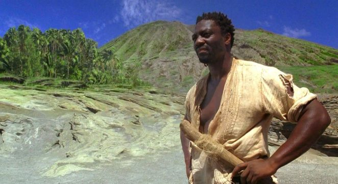 Mr. Eko stands on the beach with his hand on his hips with the mountains and forest of The Island in the distance