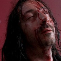 Blood on Eric's face against a red wall as he is shot to death, his expression is one of pleasure.