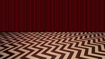 The Red Room from Twin Peaks with no furniture or people. Black and white zig-zagged floor and red curtain.