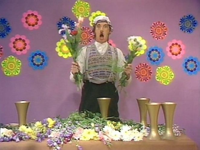 Michael Palin as Gumby prepares to stuff flowers violently into a vase