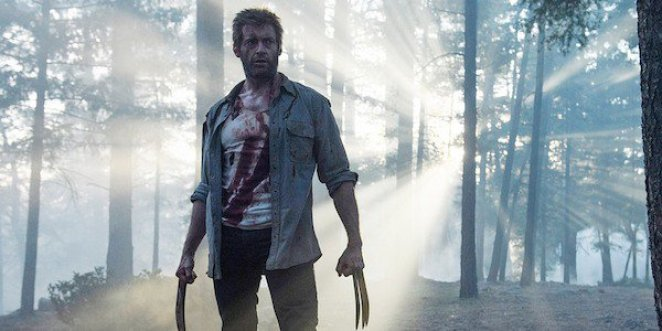 A bloodied Logan stands, claws out, in the woods
