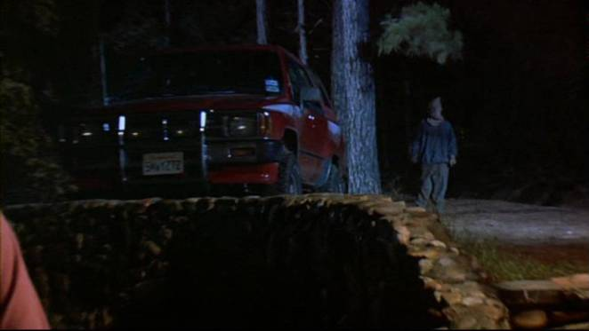 A man wearing a bag over his face stands menacingly next to a truck in the woods.