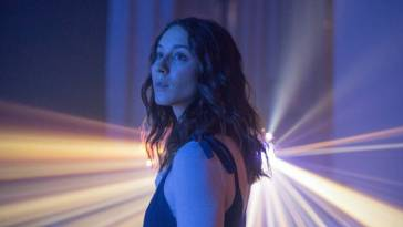 Clara (Bellisario) observes a projected starfield with wonderment.