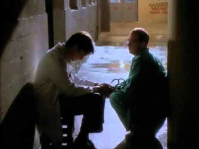 An almost sick Dr. Carter is outisde the hospital doors with his head down. Dr. Greene sits across from him offering encouragement.