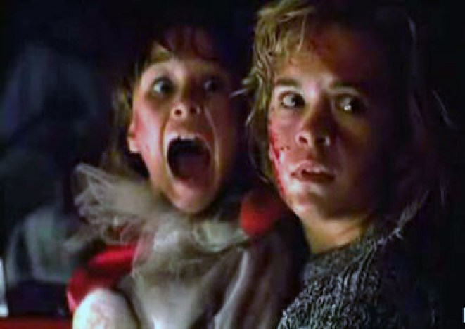 A young girl in a clown costume and teenage girl, both bloody, scream in horror while sitting in a truck.