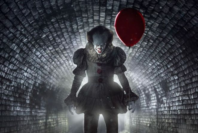 Pennywise the clown standing in a sewer holding a red balloon and grinning
