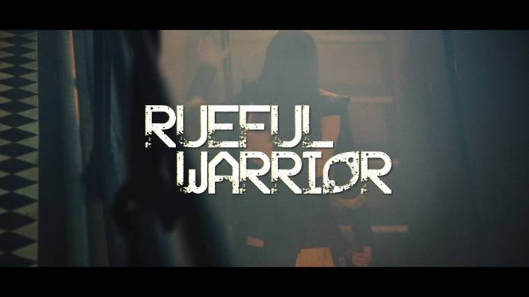 The film's title, Rueful Warrior, is superimposed over the film's opening scene: Yalalia (Michelle Fahrenheim) walking up a stairwell.