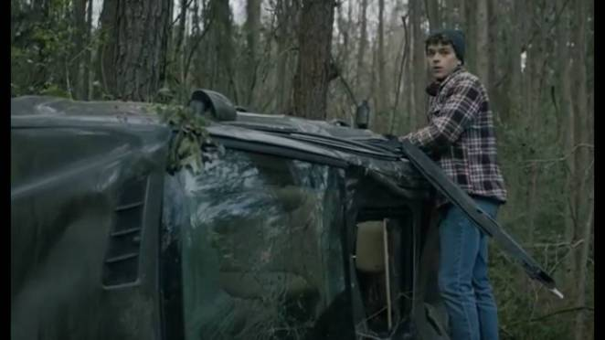 Pete stands on the side of the wreckage of a car in the woods, looking around.