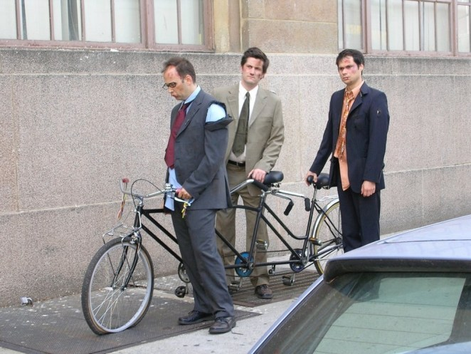 Three men in ripped up suits prepare to ride a bicycle made for three.