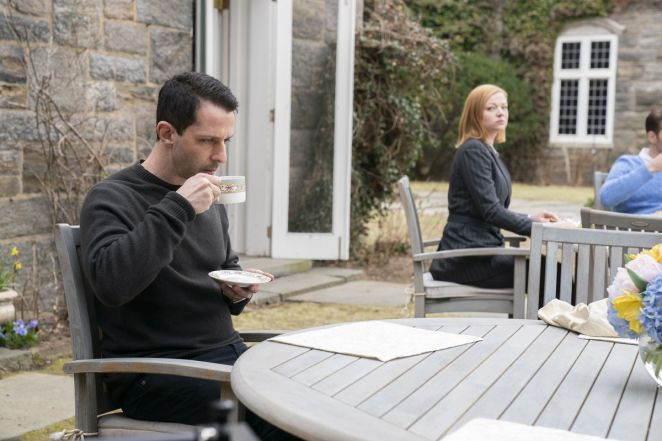 Shiv sits at a nearby table outside the Pierce house, watching Kendall as he sips coffee