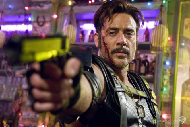 Image from the 2009 Watchmen film depicting the Comedian in a Vietnamese bar with an open bleeding gash on his cheek and jaw, aiming a revolver that he has raised toward the viewer.