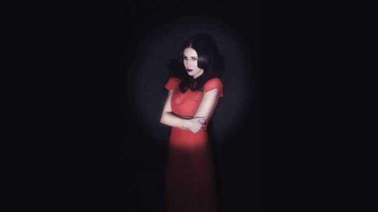 Chelsea Wolfe wearing a red dress against a black wall with a spotlight shining on her
