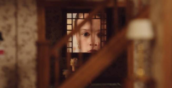 Evie looks into the window of her dollhouse as the severed doll head sits on a table in the foreground.