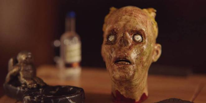 "A close-up shot of the corpse-like severed head doll from ""The House of the Head."""