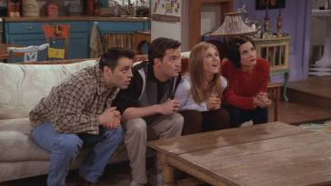 Joey, Chandler, Rachel and Monica stare intently at the TV from their couch in Monica's appartment.