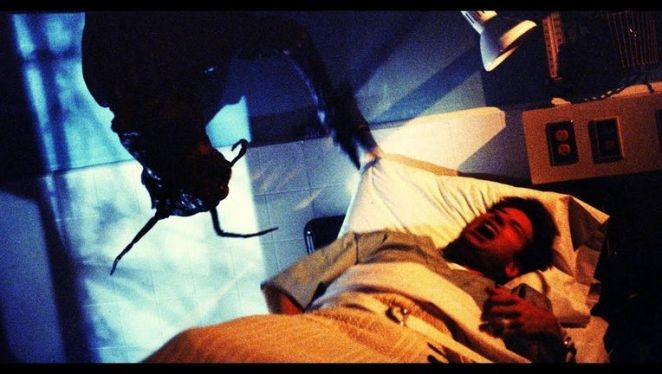 Agent Fox Mulder is screaming, restrained to a hospital bed, while the insect monster dangles above him from the ceiling.