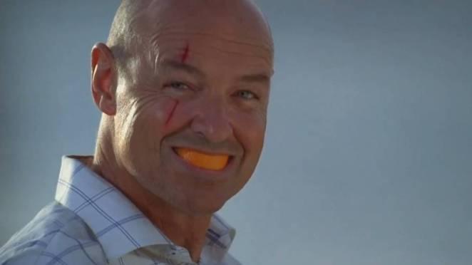 John Locke smiles with and orange rind in his mouth