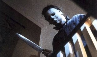 Michael Myers peering over a bannister with a large knife in his hand
