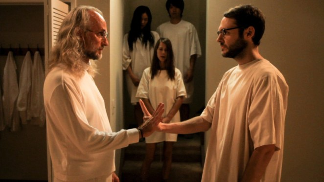 Klaus and Peter in white clothes carry out the secret handshake, with cult members watcing