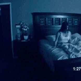 a woman sat up in bed as captured by a baby monitor