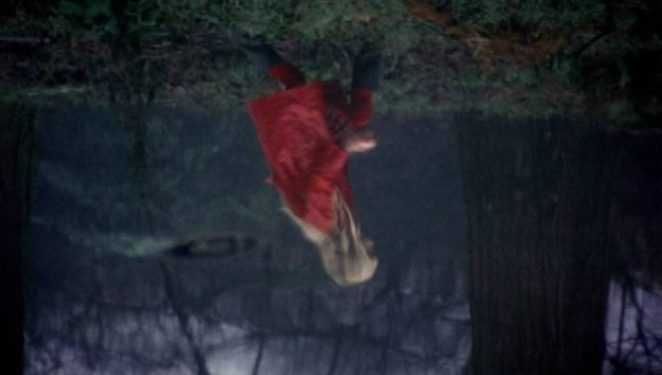 A reflection in the water of a little blonde girl wearing a red coat