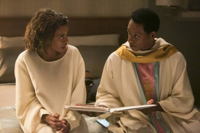 Debbie and Samuel sit on the bed, dressed in white robes, in The Knockadoo episode.