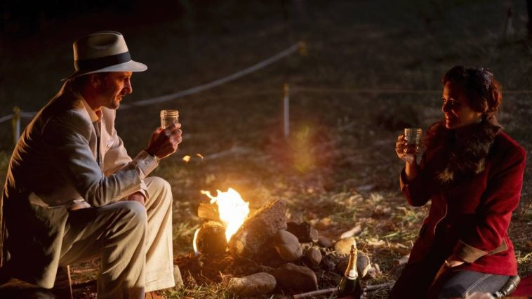 Roma and Remus sit across the campfire from each other smiling and holding jars for glasses