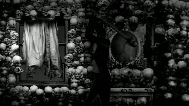 Susan Ashworth stands in a room made of skulls preparing to swing a weapon