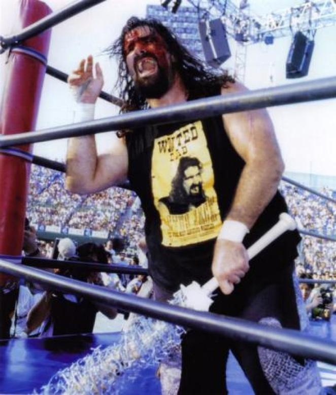 Cactus Jack kneels in a wrestling ring, bleeding from the forehead and holding a barbed wire encased baseball bat in his hand