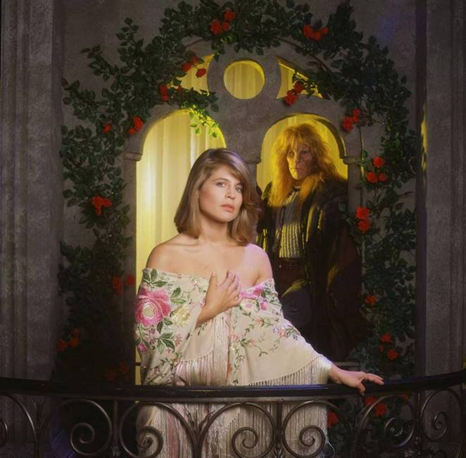 Romantic shot of Catherine on a rose-strewn balcony, as Vincent looks on over her shoulder