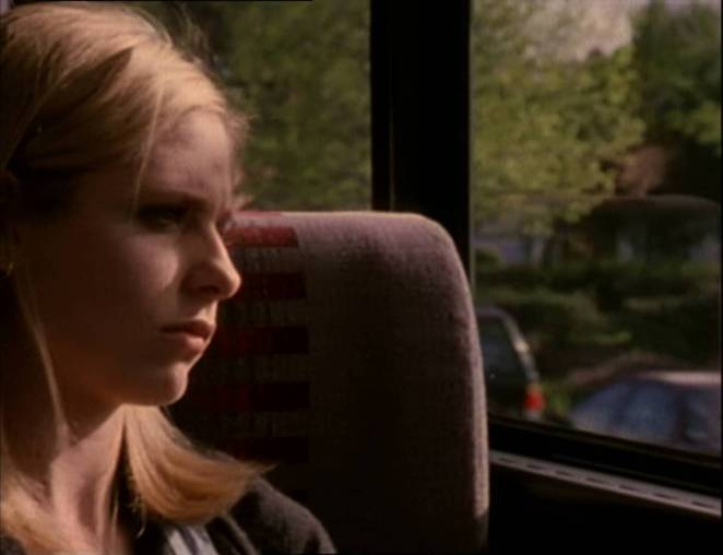 Buffy sits on a bus and looks out of the window.