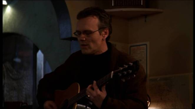 Giles plays guitar and sings at a coffee shop.