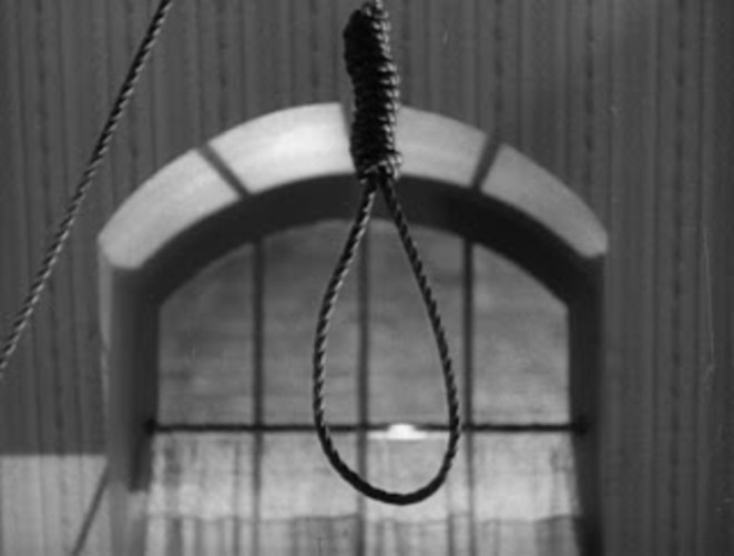 A noose hangs from a ceiling in front of a barred window
