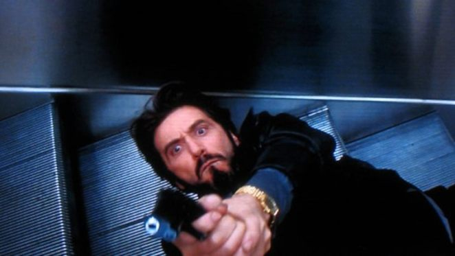 Carlito lies on an escalator putting his gun at an unseen target