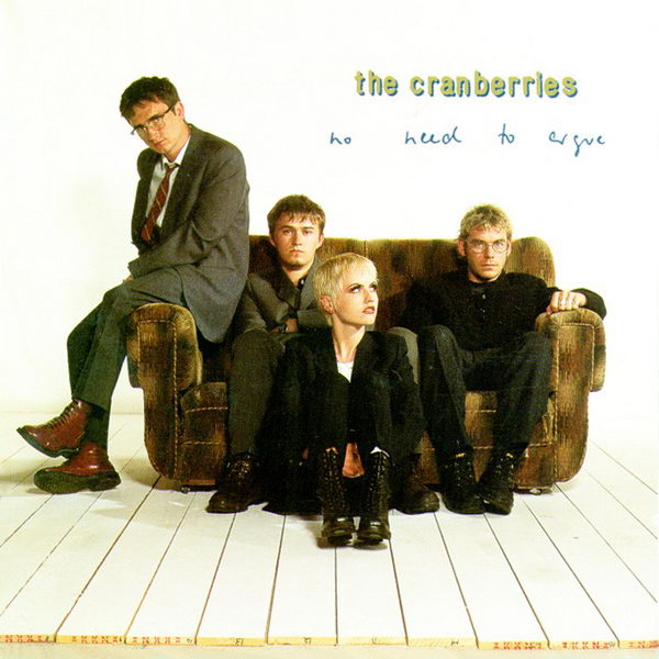 The four band members of the Cranberries look in different directions as they sit on or near a couch in a sparse white room.