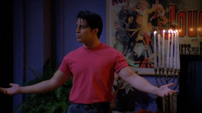 Joey, arms outstretched in a pink t-shirt, delivers an overperformed line on stage in a small theater.