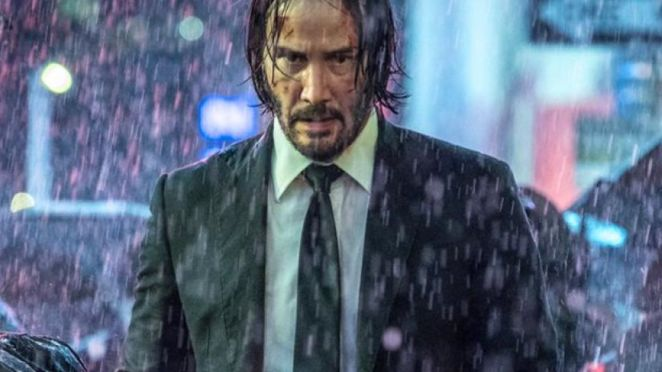 Hunted and alone, John Wick stands on rainy New York streets.