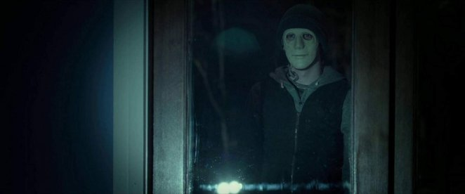 The Masked Man stands outside a window in Hush