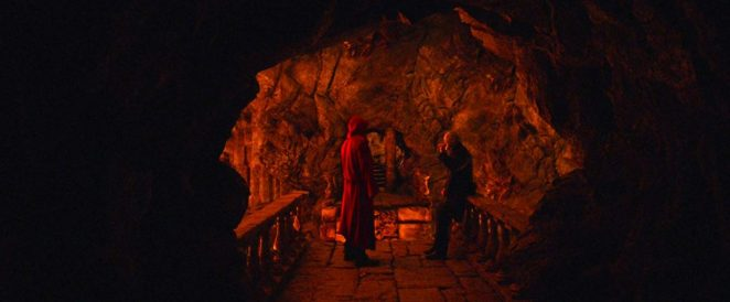 Jack and Virgil stand in a narrow cave mouth in front of a bridge
