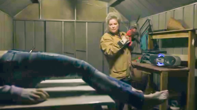 Alma stands in her shed, Danielle's frozen body in the foreground, with a small chainsaw in hand.