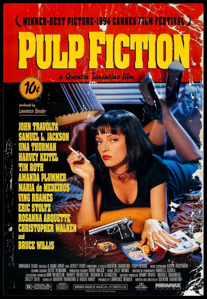 Mia Wallace lies stomach down on a motel room bed smoking a cigarette with a a gun, a pulp magazine and pack of cigarettes also on the bed