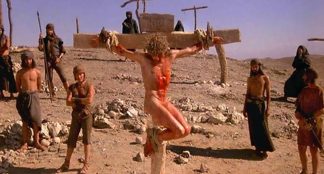 Jesus hangs from a cross bleeding naked wsurrounded by Roman guards