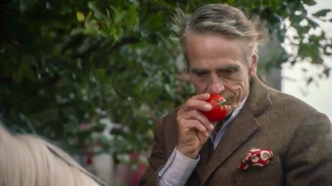 Watchmen S1E2 - The Lord of a Country Manor sniffs a tomato he has just plucked from a tree.