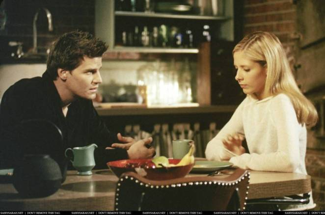 Angel and Buffy sit at a table, discussing the pros and cons of restarting their relationship. Angel wears Black and Buffy wears white, and both look gravely serious.