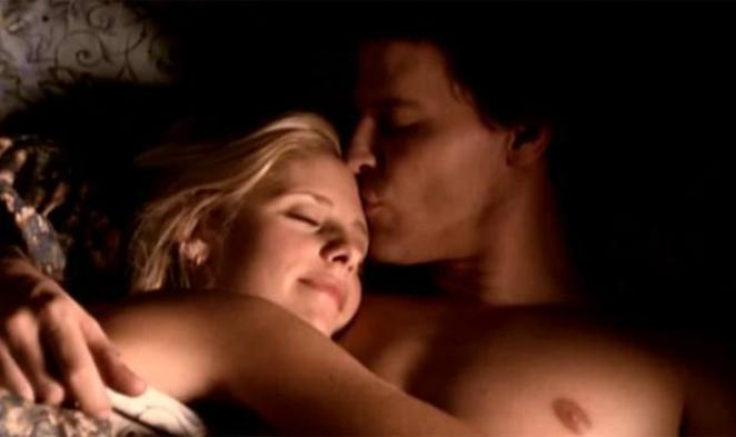 In bed, Buffy blissfully hugs a shirtless Angel while he kisses her on the forehead.
