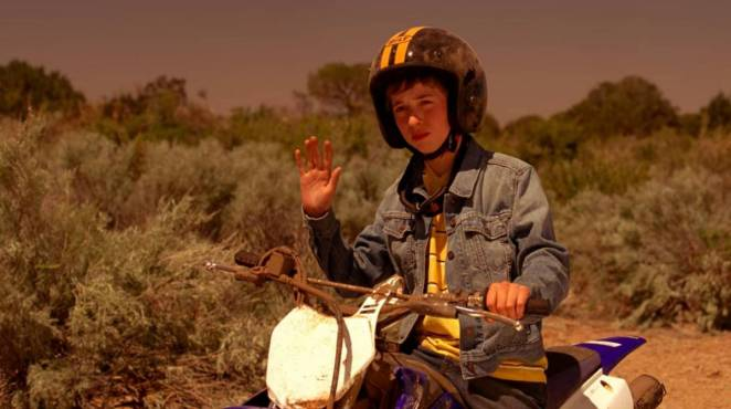 Drew Sharp sits on his dirt bike in the desert, waving to Walt, Jesse, and Todd