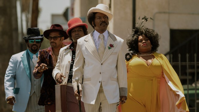 Rudy Ray Moore and his associates walk down the street dressed sharply